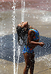 Allegra Flowers enjoys feeling the fountain at Evelyn Davis Park wash over her during a sultry summer day in Des Moines, Ia.