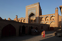 Low angle view of the  Allah Kuli Khan Madrasah, 1834-35, Khiva, Uzbekistan, pictured on July 7, 2010, in the summer afternoon light. The shadowy walkway contrasts strongly with the sunlit tiered arches of the facade in the background. The Allah Kuli Khan Madrasah, second largest college in the city, has the highest portal in Khiva. Parts of the city wall and adjoining Khojamberdiby Madrasah were demolished to allow space for the 99 celled building. Khiva, ancient and remote, is the most intact Silk Road city. Ichan Kala, its old town, was the first site in Uzbekistan to become a World Heritage Site(1991). Picture by Manuel Cohen.