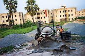 Construction workers seen working in Belgharia township outside of Dhanbad in Jharkhand, India. Families from various villages with underground fires have been rehabilitated in Belgharia township. Photo: Sanjit Das/Panos
