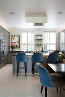 The bespoke kitchen by Mowlem, with cool grey cabinetry, incorporates concealed appliances and an island breakfast bar. A lower, built-in table provides an eating area for children.