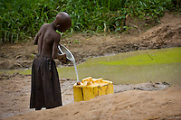 Seven yr. old Nietes pours water from the putrid pond they use as a water source in Topayero Main.Now they have a water well from International Lifeline Fund and cholera, typhoid and dysentery will no longer be a consequence of having to consume filthy water.