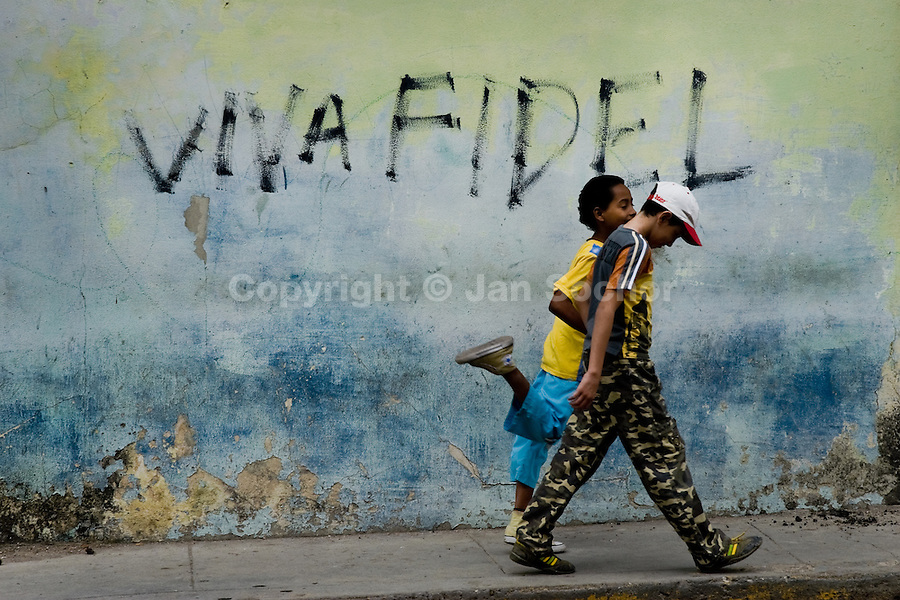 Cuban boys walk in front of a propaganda writing, painted on the wall and celebrating the Cuban leader Fidel Castro, in Havana, Cuba, 7 February 2009. About 50 years after the national rebellion, led by Fidel Castro, and adopting the communist ideology shortly after the victory, the Caribbean island of Cuba is the only country in Americas having the communist political system. Although the Cuban state-controlled economy has never been developed enough to allow Cubans living in social conditions similar to the US or to Europe, mostly middle-age and older Cubans still support the Castro Brothers' regime and the idea of the Cuban Revolution. Since the 1990s Cuba struggles with chronic economic crisis and mainly young Cubans call for the economic changes.