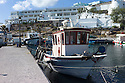 Santorini, Greece. 05.05.2014. Typical Greek fishing boats in the harbour, with Hotel Notos in the background, Vlychada, Santorini, Greece. Photograph © Jane Hobson.