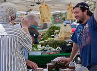 A smiling vendor talks to three women.  SR.