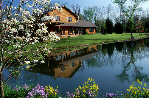 Rural cedar wood home in spring reflected in lake with blooming spring dogwood and wildflowers