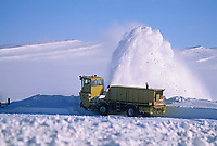 High winds blow drifting snow across the James Dalton Highway north of the Brooks Mountain Range, on Alaska's Arctic Coastal Plains. Alaska department of transportation worker removes snow drifts with blower.