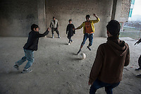 The Chamne Babrak refugee camp in Kabul 5-1-14 Boys from the camp play football in a disused building.