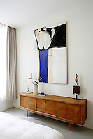 In the master bedroom a painting by the artist Eléonore de la Taste hangs above a Danish sideboard