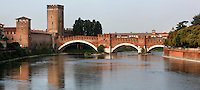 Panoramic view of the crenellated bridge of the Castelvecchio crossing the Adige River and, on the left Castelvecchio, 1354-79, Verona, Italy. The castle, built with its bridge, for Cangrande II, stands on the probable site of a Roman fortress. The fortified bridge was intended as an emergency escape route for the Scala family towards the Tyrol. The castle, where Napoleon stayed, was damaged  during the Pasque Veronesi, Napoleonic Wars (1796-97). Castelvecchio was restored in 1923 and 1963-65. Picture by Manuel Cohen.