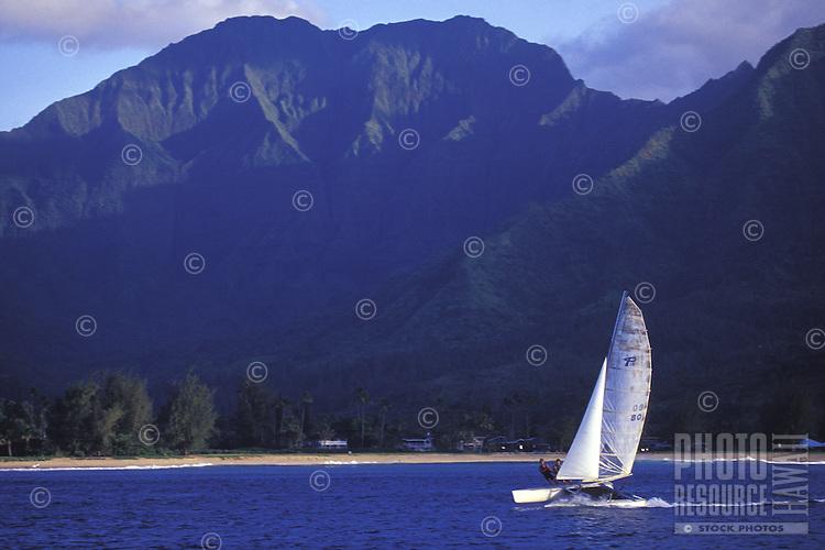 Catamaran sailing in tradewinds with beach and Mount Waialeale in background, on Hanalei Bay, Kauai