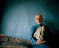 """51 year old Sabit from Kosovo sits with his asylum papers in a tiny box room paid for by relatives in Hounslow. He claimed asylum in 2003 and was refused the same year. He is destitute and relies on his relatives to support him. He had been working as a senior tax officer in the Ministry of Finance in his country when he was falsely accused of being a Serb collaborator. He received death threats saying that if he didn't leave the country immediately he would be killed. He is diabetic and struggles to find the right foods to eat because he only has the money his relatives give him to survive on. He does voluntary work for the Citizens Advice Bureau and spends a lot of time in the library reading. """"I would give anything to be reunited with my friends and family and to be able to work in this country,"""" he says. Sabit is one of an estimated 300,000 rejected asylum seekers living in the UK. .. ."""