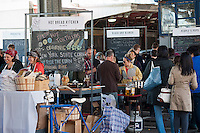 """Customers shop at the New Amsterdam Market on South Street in New York during the market's opening day for the season, Sunday, April 29, 2012. The market, located in the former Fulton Fish Market, features vendors who source their artisanal food directly from local farmers and stands of the farmers'  themselves . For opening day they promoted their """"Bread Pavilion"""" which had booths from 16 local artisanal bakeries. (© Richard B. Levine)"""