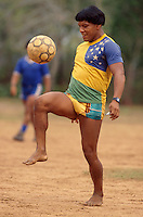 Acculturated brazilian indian, Yaulapiti indigenous people play soccer, wears Brazil soccer team shirt and watch at Xingu National Park. Mato Grosso State, Amazon rainforest, Brazil.