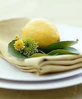 This place setting is decorated with a lemon, lime leaves and chrysanthemums