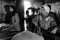 State of Palestine. West Bank. Balata Camp. Palestinian refugees. A groups of cutomers ( a woman, a young moslem teenage woman wearing a Hijab and a few boys) wait to buy their bread at the bakery. A Hijab, also spelled ḥijāb, is a veil that covers the head and chest, which is often worn by Muslim women beyond the age of puberty in the presence of adult males outside of their immediate family as a form of modest attire. Balata Camp is a Palestinian refugee camp established in the northern West Bank in 1950, adjacent to the city of Nablus. It is the largest refugee camp in the West Bank. Balata Camp is densely populated with 30,000 residents in an area of 0.25 square kilometers. In 1991, Balata Camp was living under Isreal's occupation and rules as part as the Occuppied Territories. In the 1980s and 1990s, Balata residents played a leading role in the uprisings known as the First Intifada and the Second Intifada. Balata Camp is since 1993 under palestinian authority, located in the A zone. The Palestinian National Authority (PA or PNA) was the interim self-government body established to govern Areas A and B of the West Bank as a consequence of the 1993 Oslo Accords. Following elections in 2006, its authority had extended only in areas A and B of the West Bank. Since January 2013, the Fatah-controlled Palestinian Authority uses the name State of Palestine on official documents. © 1991 Didier Ruef