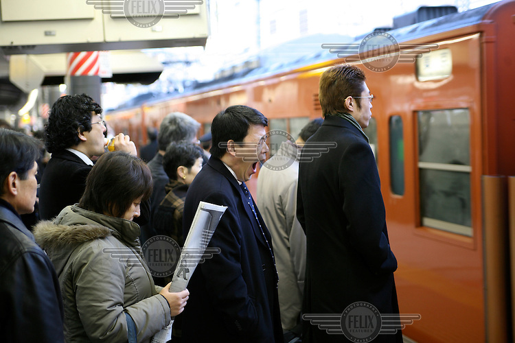 Early morning commuters at Shinjuku Station wait to board a Chuo Line train into Tokyo. JR (Japan Railways) has 16 tracks at Shinjuku Station and there are 38 tracks if you include the subway and metro lines along with the private railway companies Odakyu and Keio. Shinjuku train station is the busiest in the world with approximately 3.3 million people passing through the station everyday. .