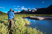 Photographing the view over mountain range from Engerdine Lodge grounds, Spray Valley Provincial Park, Alberta, Canada
