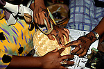 Zanzibar, Tanzania. Women with hands decorated with intricate henna tattoo designs wrapping a basket.