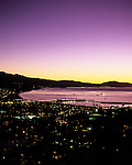Santa Barbara at sunrise with city lights along the Pacific Ocean beach with Stearns Wharf and Santa Ynez Mountain Range in background Santa Barbara California USA