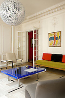 There are unique works of art all over the apartment; here in the living room a framed poster by Fernand Leger hangs above the vintage sofa and the coffee table is a unique powder-pigment piece by Yves Klein