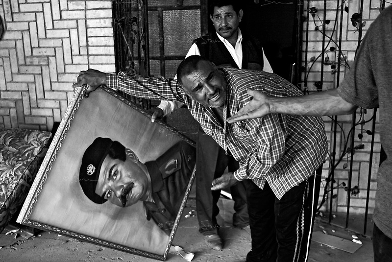 Baghdad, Iraq, April 10, 2003.In the house of Watban, Saddam Hussein's half brother, looters spit and shout insults to a canvas painting of the fallen tyran. On the morning after the entry of US Army in Baghdad, thousands of baghdadis from the poorer quarters of the city started to loot all official buildings houses of important people of Saddam's regime.