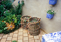 Two woven wicker compost bins on stone patio next to wall, garden plants, with worm ornaments to make composting attractive to children and the family.