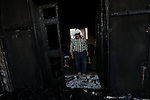 A Palestinian man inspects a house that was badly damaged from a suspected attack by Jewish extremists on two houses at Kafr Duma village near the West Bank city of Nablus July 31, 2015. The house had been empty and there were no casualties there. The fire in the other house killed an 18-month-old Palestinian child, injured a four-year-old brother and both parents on Friday, Israeli security officials said. The three injured people from the other house were taken to Israeli hospitals, officials said. Photo by Ahmad Talat