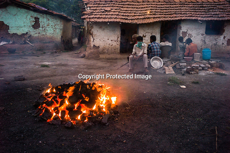 Villagers sit next to the pile of coking coal in Bokapahari village in Jharia, outside of Dhanbad in Jharkhand, India.  Photo: Sanjit Das/Panos