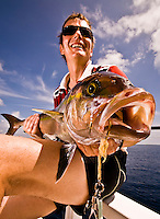 Maldives Islands, Indian Ocean November 2008. Fisherman in his 40s holding an Amberjack (Seriola rivoliana), a member of the carangide family found in all temperate waters.