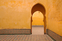 Horseshoe arched doorway in a room with apricot stucco walls and zellige tiled floor in the Mausoleum of Moulay Ismail, or Moulay Ismail Ibn Sharif, reigned 1672ñ1727, second ruler of the Alaouite dynasty, built 1703 by Ahmed Eddahbi, Meknes, Meknes-Tafilalet, Morocco. Meknes is a fortified Imperial city redeveloped under Sultan Moulay Ismail, 1634-1727, as Morocco's political capital. Picture by Manuel Cohen