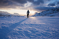 Female hiker with snowshoes on way to Ryten, Moskenesøy, Lofoten Islands, Norway