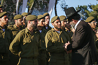 A Rabbi has words with an ultra-Orthodox Jewish soldier from the Netzah Yehuda Battalion in the Israeli army during their swearing-in ceremony on Ammunition Hill in Jerusalem