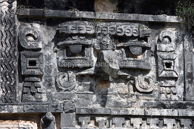Mask of Chaac, god of the rain, with a sculpture of a man between the two eyes and the symbol of corn (¤) above the mask, The Monastery, Puuc architecture, 750-900 AD, Chichen Itza, Yucatan, Mexico. Picture by Manuel Cohen