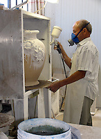 Man spraying glaze on pottery piece in spray booth at a ceramics factory in Deruta, Italy