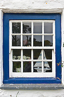 Sailing yacht and vase of flowers in bright blue window of Rose Cottage at Helston in Cornwall, UK