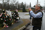 NEWTOWN, CT-17 December 2012-121712LW08 - Mihail Gladuhov of Torronto, Canada, takes a picture of evergreen memorials near the entrance of Sandy Hook Elementary School  in Newtown Hill Road Monday. Gladuhov is a truck driver who stopped by the site at the request of his nine-year-old daughter to place a teddy bear for the victims of the shooting. Laraine Weschler