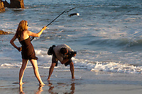 A photographer and his lighting assistant work in front of the waves at the south/east end of Corona Del Mar State Beach, just below Inspiration Point.