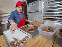 STAFF PHOTO JASON IVESTER --11/26/2014--<br /> Jeanette Greer dips caramel pieces into chocolate on Wednesday, Nov. 26, 2014, inside Martin Greer's Candies in Garfield.