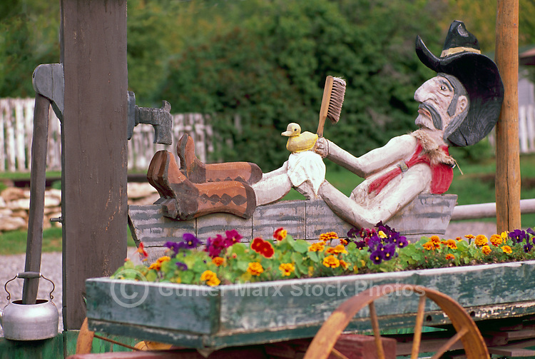 Cowboy bathing in Bathtub Wood Carving, and Old Wagon Carriage recycled for reuse as Flower Garden, Cariboo Chilcotin Region, BC,  British Columbia, Canada, Summer
