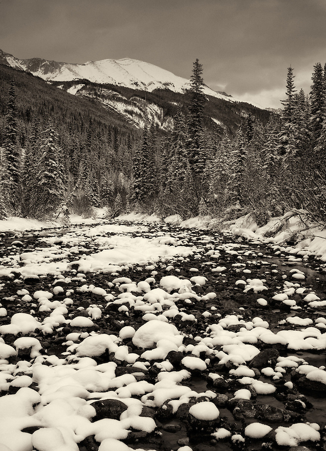 A river is filled with snow-covered rocks on this gray winter day in Banff National Park in Alberta, Canada.