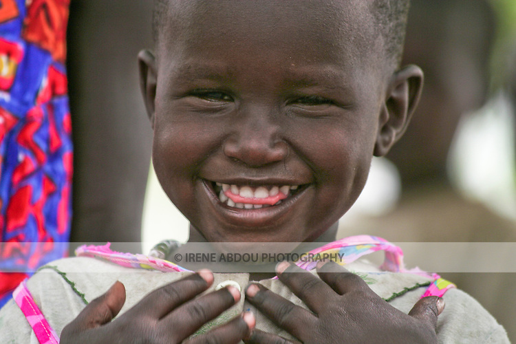 A girl in Rumbek, South Sudan joyfully looks the camera in the eye.  These are her very first photos.