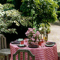A red and white striped tablecloth transforms a garden table for an impromptu lunch