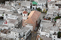 Rooftops and Iglesia Parroquial de la Santa Cruz (Parish Church of the Holy Cross), 16th century, Pampaneira, in the gorge of the Poqueira river, Alpujarra, Andalucia, Southern Spain. Moorish influence is seen in the distinctive cubic architecture of the Sierra Nevada's Alpujarra region, reminiscent of Berber architecture in Morocco's Atlas Mountains. Photograph by Manuel Cohen.