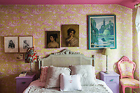 The walls of a guest bedroom are lined with a pretty toile de Jouy paper decorated with an assortment of artwork
