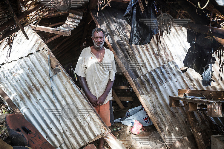 Amon in front of the remains of his family's house, which was badly damaged, on 13 March 2015, by Cyclone Pam. Now the family of five live in a tent provided as part of an international emergency aid effort.