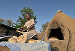 A man bakes bread in the Khamsadegaig camp for internally displaced families, where victims of the conflict in Sudan's Darfur region have taken refuge. ACT-Caritas supports families here with a variety of services, including potable water, sanitation, and income generating opportunities--such as baking bread.