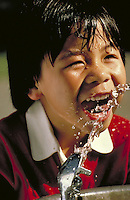 CHINESE-AMERICAN BOY DRINKING AT WATER FOUNTAIN IN GOLDEN GATE PARK, SAN FRANCISCO. CHINESE AMERICAN BOY. SAN FRANCISCO CALIFORNIA USA GOLDEN GATE PARK.