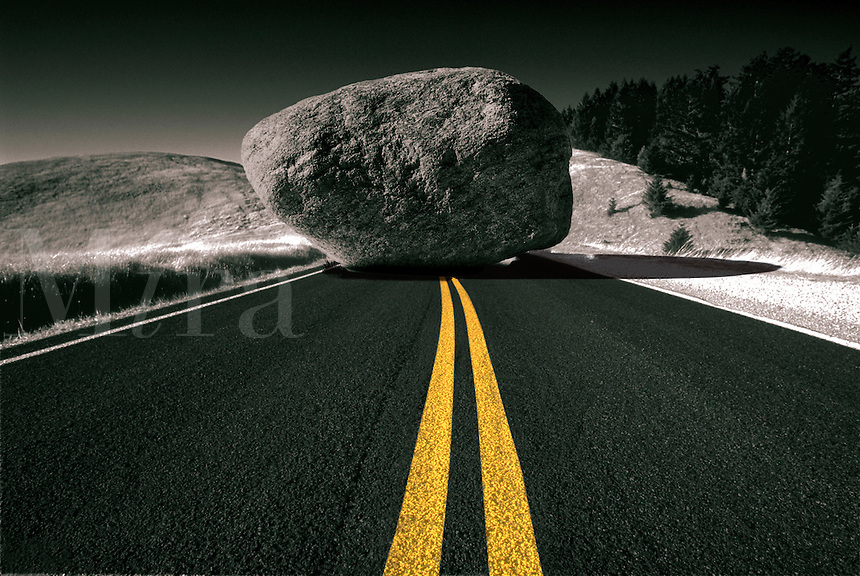 Yellow lane divider leading up to a boulder blocking the road.
