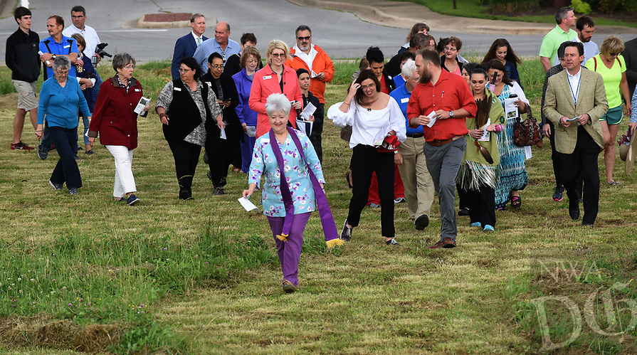 NWA Democrat-Gazette/FLIP PUTTHOFF <br /> GARDEN BLESSING<br /> Rev. Pamela Cicioni, spiritual director at Highlands Oncology Group in Rogers (center), leads a blessing of the land walk Wednesday May 17 2017 at the site of the Healing Gardens of Northwest Arkansas. The garden will be built near the west entrance of Highlands Oncology Group on South 52nd Street. In addition to flowers, plants and trees, the garden will feature a waterfall, reflecting pool, sanctuary and walkways. The garden property is adjacent to the Razorback Greenway and will be open to the public. A fundraising campaign will begin soon to help fund construction, Cicioni said. An estimated completion date has not been set. The blessing walk featured music and readings at various sites where garden features will be built.
