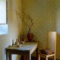A simple wooden chair and table stand in the corner of a room with hand-printed walls
